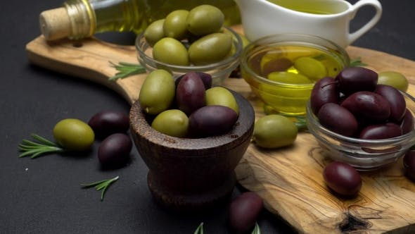 Cover Image for Black and Green Olives and Oil on Wooden Cutting Board