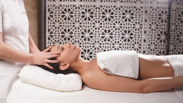 Thumbnail for Young Woman with Black Hair Is Getting Relaxing Massage in Beauty Salon.