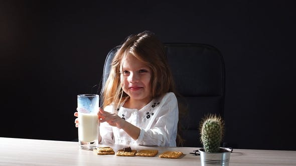 Thumbnail for Happy Beautiful Little Girl Having a Snack with Milk and Cookies.