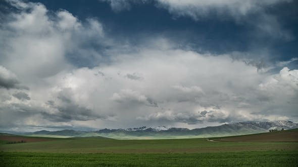 Cover Image for Green Meadow and Mountains on the Horizon at Clouds.