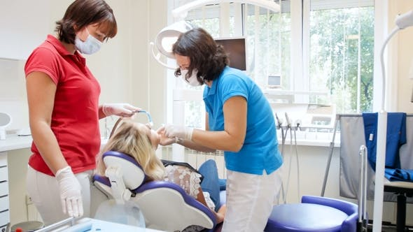 Thumbnail for Video of Dentist with Nurse Treating Young Woman Sitting in Dental Chair