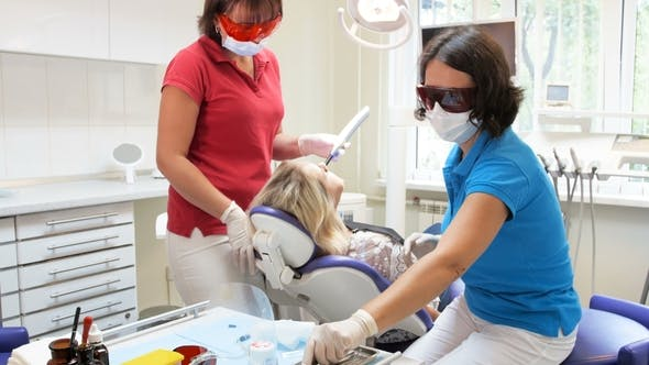 Thumbnail for Dentist and Assistant Treating Patient's Teeth with Curing Photopolymer