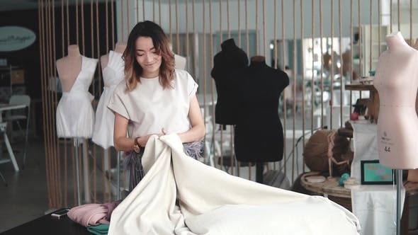 Thumbnail for Young Woman Working in a Sewing Studio. Girl Designer Clothes Scraps Cloth on the Table