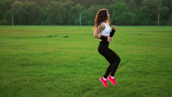 Thumbnail for Sporty Girl in a White Top and Pink Sneakers Makes the Warm-up on the Grass
