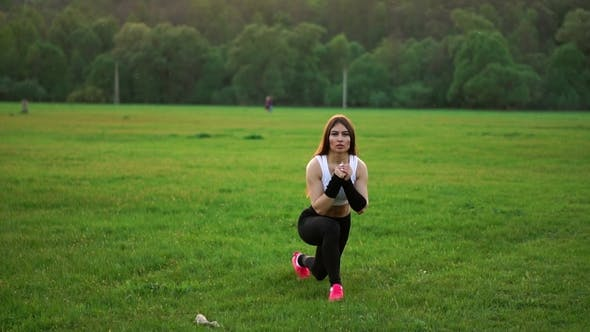 Thumbnail for Sporty Brunette in a White Top and Black Tight Pants and Pink Sneakers in the Sunlight Stretches