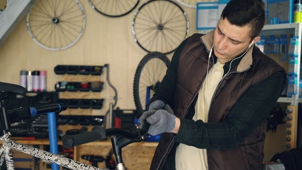 Busy Serviceman Is Disassembling Cycle Handlebar and Cleaning Parts