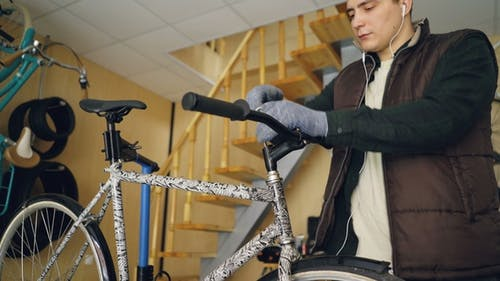 Focused Male Mechanic Listening to Music with Earphones while Fixing Bicycle Handlebar