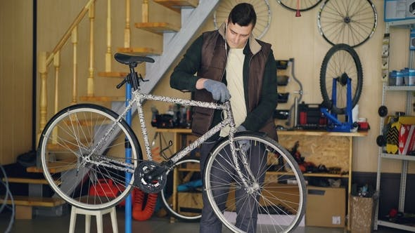 Young Maintenance Man Is Assembling Bicycle Placing Stearing Wheel and Fixing It