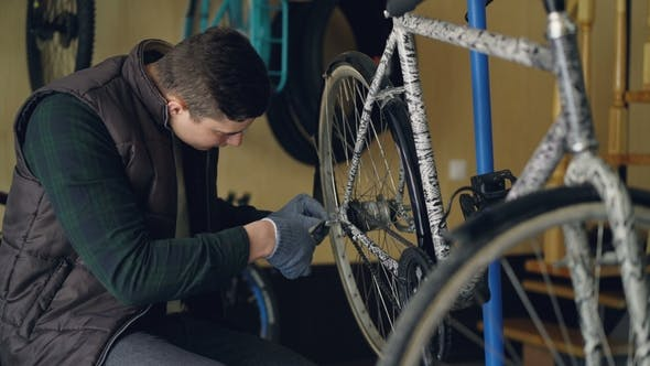 Handsome Male Serviceman in Gloves Is Repairing Back Wheel of Bicycle Using Professional Tools