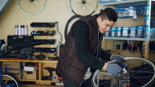 Handsome Mechanic Cleaning Bicycle Wheel Outside and Inside