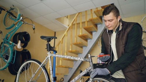 Serious Repairman Fixing Bicycle with Screw Wrench and Listening To Music through Earphones