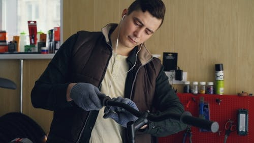 Concentrated Mechanic in Gloves and Warn Vest Is Listening to Music with Earphones