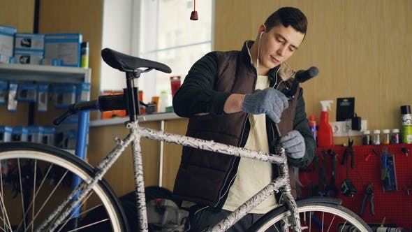 Focused Mechanic Assembling Bicycle Placing Handle-bar Then Tightening Joints with Key