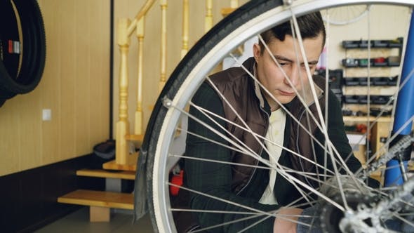 Young Man Experienced Serviceman Is Fixing Bike Wheel Using Wrench and Tools. Small Cozy Workshop