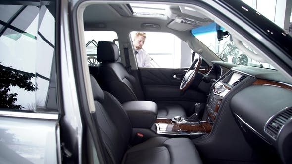 Thumbnail for Young Male Customer Sitting Down in New Car in Auto Showroom