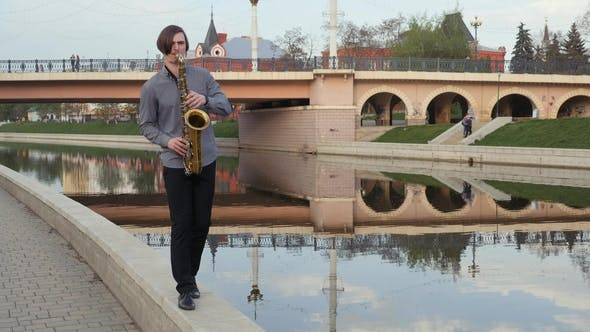 Thumbnail for Young Man Plays the Saxophone. The Musician Plays on the Wind Instrument