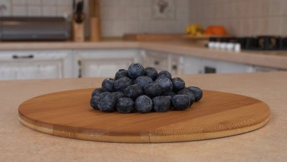Thumbnail for Several Blueberry Berries on the Bamboo Plate. Rotating Camera with White Kitchen on the Background