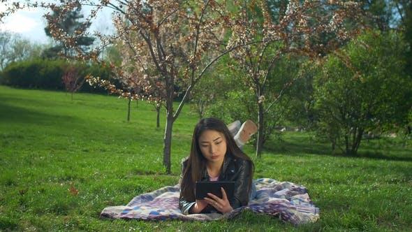 Thumbnail for Lächelnde junge Frau legen auf Rasen mit Tablet Pc