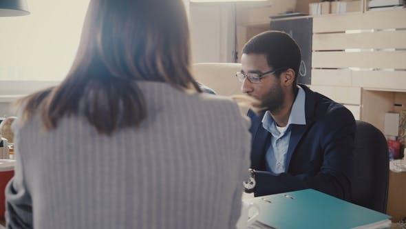 Thumbnail for Zwei nervöse Afroamerikaner Manager sitzen am Tisch, hören Unerkennbare weibliche Anwältin bei