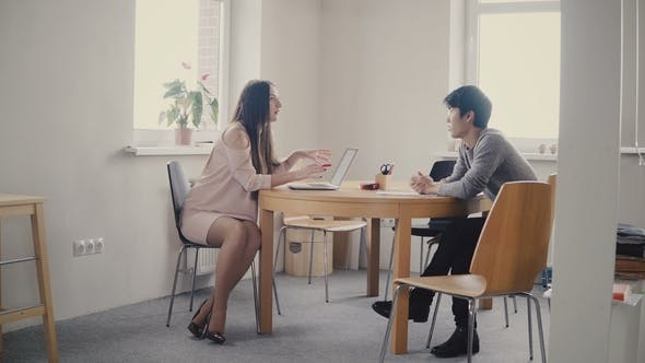 Young Asian Man Talking To Confident Businesswoman By the Table. Multiethnic People Talk in Trendy