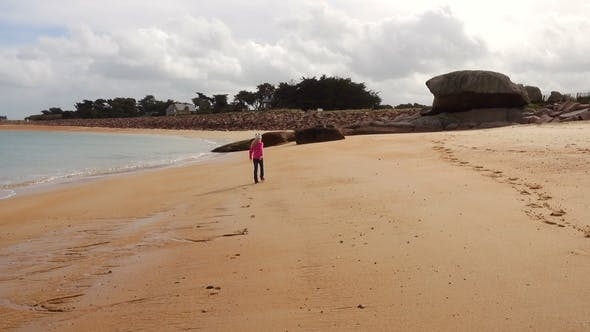 Thumbnail for Child Girl Walking and Playing on an Empty Beach