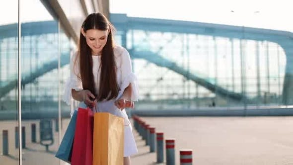 Thumbnail for Pretty Fashion Model in White Dress Poses with Shopping Bags Before a Modern Glass Building