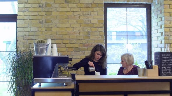 Thumbnail for Barista and Mature Woman Intern Make Coffee on the Bar in Cafe