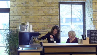 Barista and Mature Woman Making Coffee on the Bar in Cafe