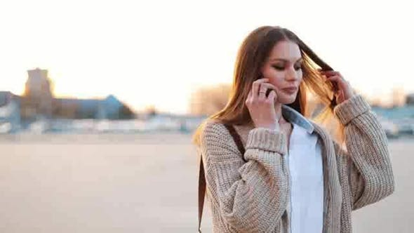 Thumbnail for Young Woman with Long Hair Walks Along the Street and Talks on the Phone