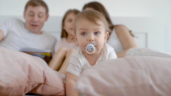 Baby Child with Pacifier Looking Concentrated