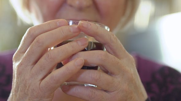 Thumbnail for Mature Woman Holds Cup with Coffee in Hands