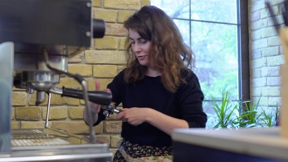 Barista Tamping Grinded Coffee inside of Portafilter