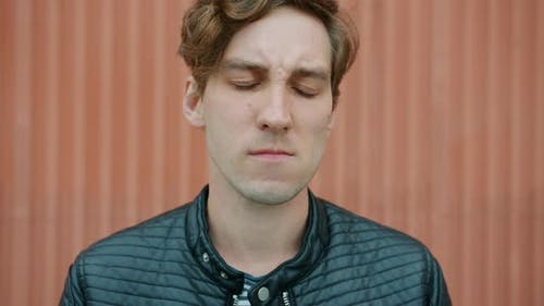 Slow Motion Portrait of Unhappy Young Man Touching Cheek Suffering From Toothache Outdoors