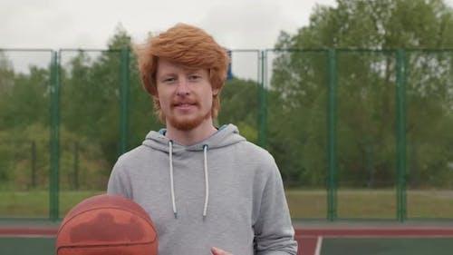 Junger Mann posiert mit Basketball im Freien