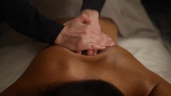 Cover Image for Close Up Spa Hotel Massage Woman Back. Therapist Hands Do Massage To a Woman in a Dark Room with