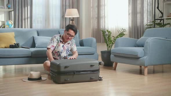 Man Packing His Clothes And Closing His Suitcase In The Living Room He Preparing For Vacation Trip