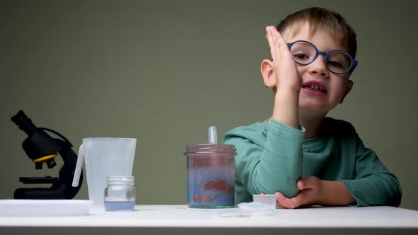 Cover Image for Alternative School. Boy in Glasses Doing Experiment. Young Scientist Mixing Up Licquid for
