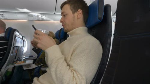 Young Man Looks at Phone While Sitting on Plane Drinks Water