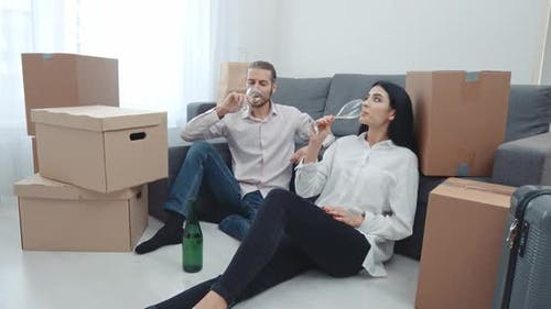 Moving To a New Apartment, a Young Couple Sitting on the Floor Near Boxes of Things and Drinking