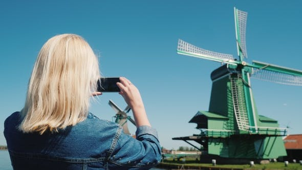 Thumbnail for A Woman Takes Pictures of Old Windmills in Holland, Uses a Smartphone. Traveling in the Netherlands