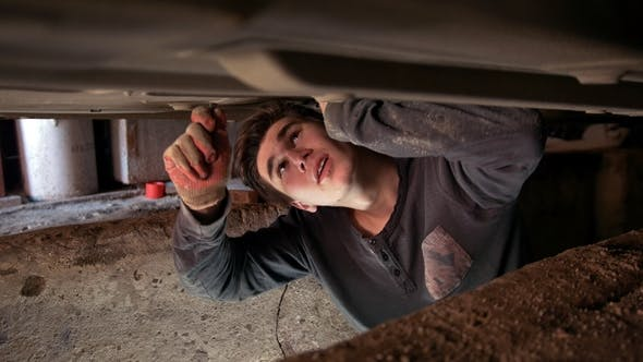 Thumbnail for Young Man Underneath a Car Repairs His Car in the Garage Pit