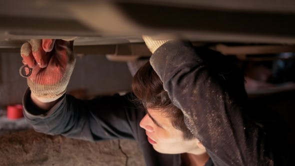 Thumbnail for Male Auto Mechanic Underneath a Car Screwing Components in the Garage