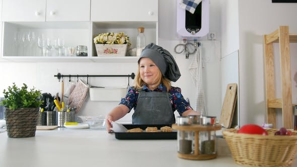 Thumbnail for Preschool Girl Baker Holding a Baking Sheet with Cookies