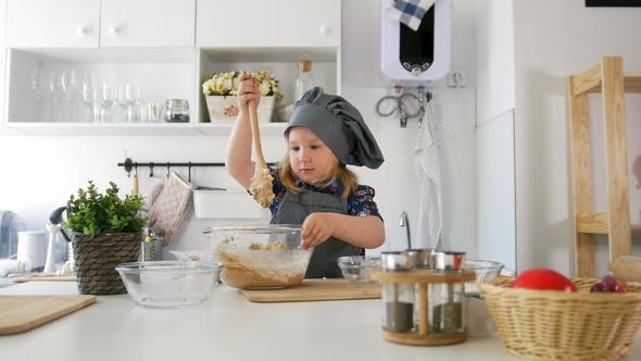 Thumbnail for Preschool Girl Baker Kneads the Dough with a Large Wooden Spoon in a Bowl
