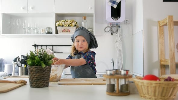 Thumbnail for Cheerful Little Girl in Apron Rolls Out the Dough in the Kitchen