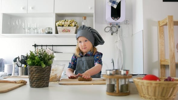 Thumbnail for Little Caucasian Girl in Apron Rolls Out the Dough on the Board