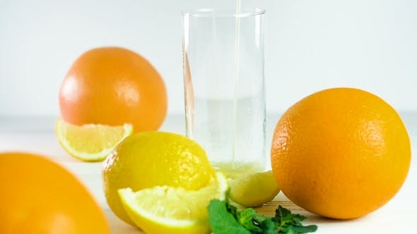 Thumbnail for Footage of Pouring Orange Juice in Glass on White Wooden Table Next To Assortment of Citrus Fruits