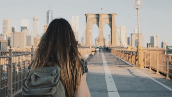 Thumbnail for Young Woman with Backpack Walking Along Brooklyn Bridge
