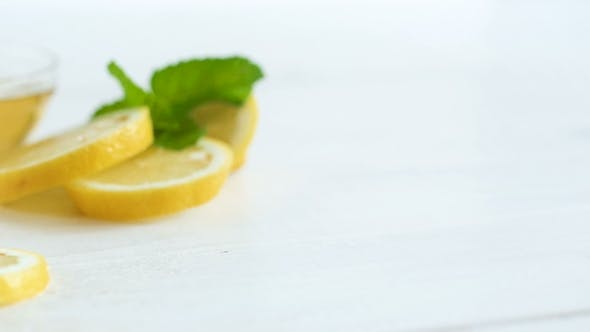 Thumbnail for Camera Panning Along Lemons, Leaves of Mint and Jar with Bee Honey on White Wooden Table