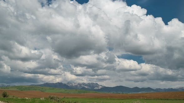 Cover Image for Fields and Storm Clouds Over Mountains